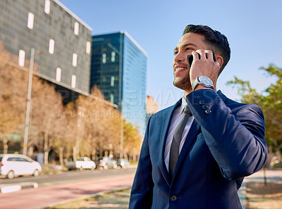 Buy stock photo Shot of a young businessman talking on his cellphone while out in the city