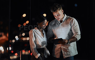 Buy stock photo Shot of two businesspeople using a digital tablet together outside an office at night