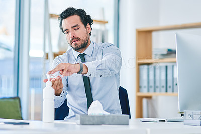 Buy stock photo Shot of a young businessman using hand sanitiser while working in an office