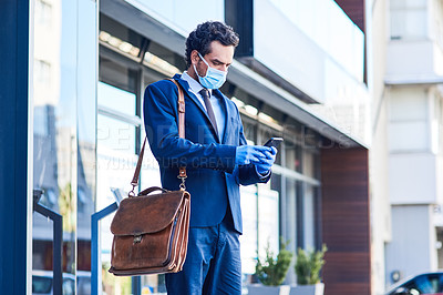 Buy stock photo Shot of a young businessman wearing a mask and using a cellphone while out in the city