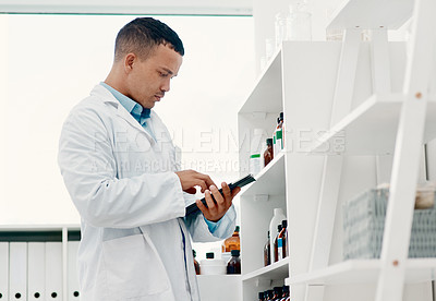 Buy stock photo Shot of a young scientist using a digital tablet while analysing medication in a laboratory