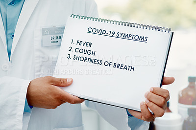 Buy stock photo Cropped shot of a scientist holding a sign with a list of COVID-19 symptoms on it in a modern laboratory