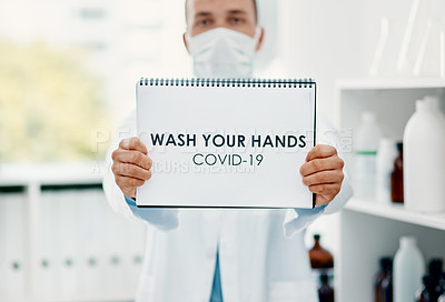 """Buy stock photo Shot of a scientist holding a sign with """"wash your hands"""" on it in a laboratory"""
