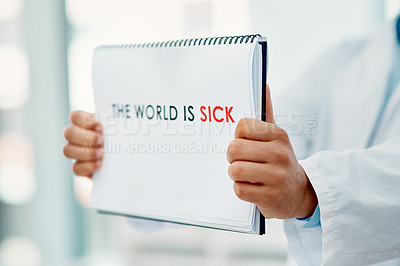"""Buy stock photo Shot of a scientist holding a sign with """"The world is sick"""" on it in a laboratory"""