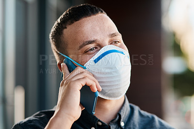 Buy stock photo Shot of a young businessman wearing a mask and using a smartphone on the balcony of an office