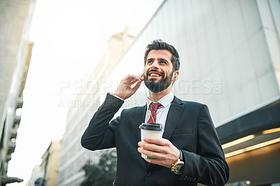 Buy stock photo Shot of a businessman wearing earphones and holding a coffee while out in the city