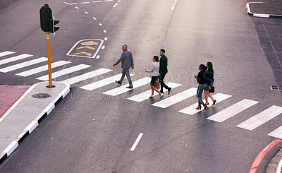 Buy stock photo Shot of a group of businesspeople walking across a pedestrian