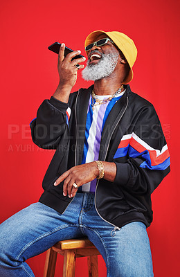 Buy stock photo Studio shot of a mature man using his cellphone against a red background