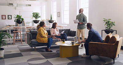 Buy stock photo Shot of a mature businessman leading a discussion with his colleagues in an office