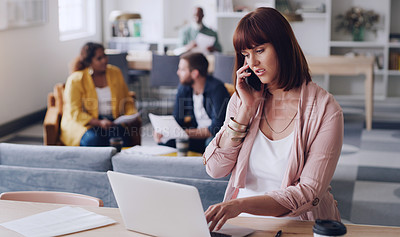 Buy stock photo Shot of a young businesswoman talking on a cellphone while using a laptop in an office