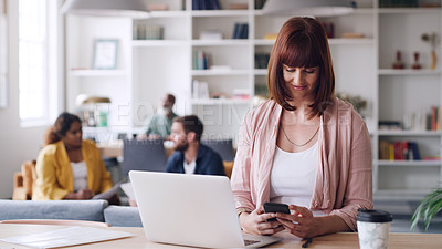 Buy stock photo Shot of a young businesswoman using a laptop and cellphone in an office