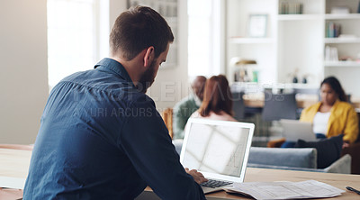 Buy stock photo Rearview shot of a young businessman working on a laptop in an office