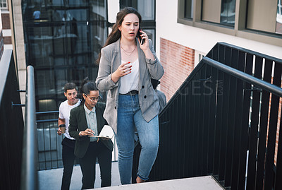 Buy stock photo Shot of a young businesswoman looking using a smartphone while walking up the stairs in a modern workplace