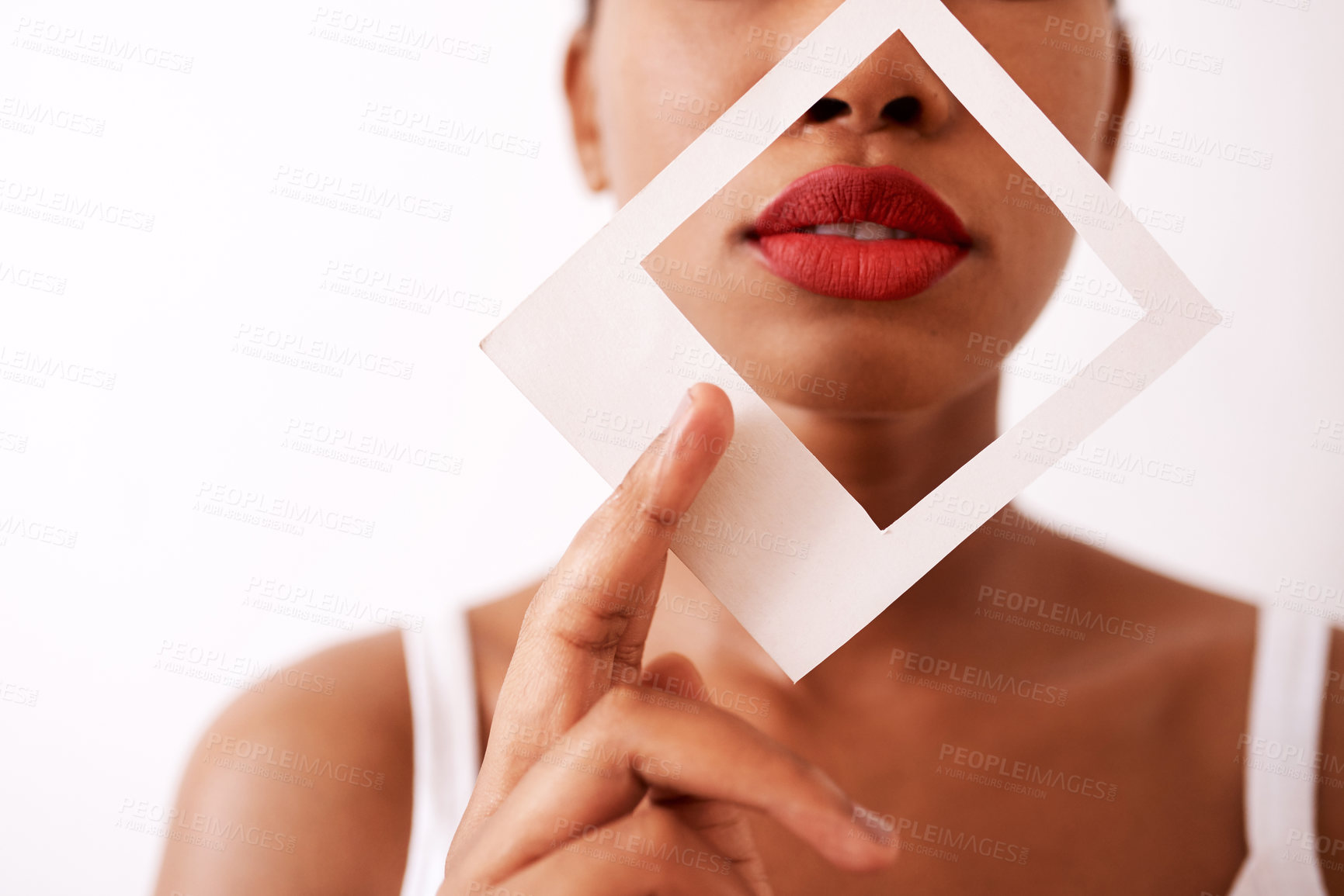 Buy stock photo Studio shot of an unrecognizable woman holding a frame over her red lips