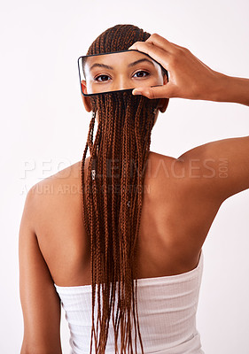 Buy stock photo Studio shot of a woman holding up a picture on a cellphone behind her head