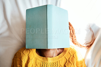 Buy stock photo Shot of an unrecognizable woman lying with a book over her face