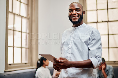 Buy stock photo Shot of a young businessman using a digital tablet with his colleagues in the background