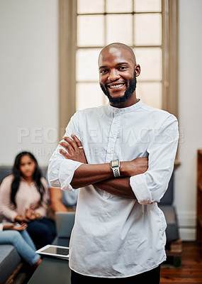 Buy stock photo Portrait of a young businessman working in a modern office with his colleagues in the background
