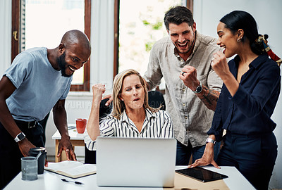Buy stock photo Cropped shot of a group of business colleagues cheering while gathered around a laptop in the office