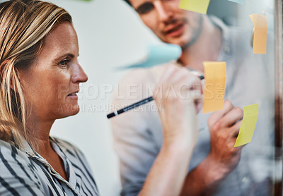 Buy stock photo Cropped shot of two business colleagues brainstorming on a glass wipe board in their office