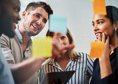 Buy stock photo Cropped shot of a group of business colleagues brainstorming on a glass wipe board in their office