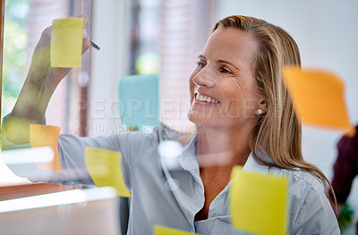 Buy stock photo Shot of a mature businesswoman writing notes on a glass wall in an office