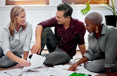 Buy stock photo Shot of a group of businesspeople brainstorming with notes on a floor in an office
