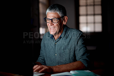 Buy stock photo Shot of a senior businessman working on a computer in an office at night