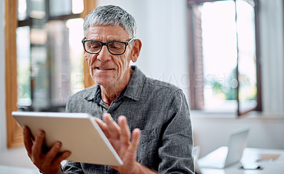 Buy stock photo Shot of a senior businessman using a digital tablet in an office