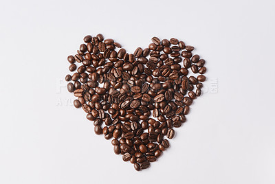 Buy stock photo Studio shot of coffee beans shaped in a heart against a white background