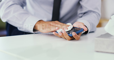 Buy stock photo Closeup shot of an unrecognisable businessman using a disinfecting wipe to clean a cellphone in an office
