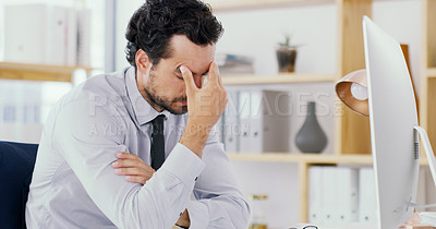 Buy stock photo Shot of a young businessman looking stressed out while working on a computer in an office