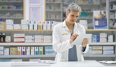 Buy stock photo Shot of a mature female pharmacist using a digital tablet while working behind the counter in a chemist