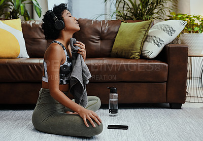 Buy stock photo Shot of a young woman wiping her neck with a towel while exercising at home