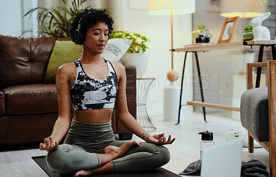 Buy stock photo Shot of a young woman wearing headphones and using a laptop while practising yoga at home
