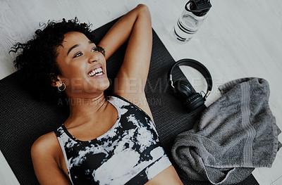 Buy stock photo High angle shot of a young woman lying on an exercise mat at home