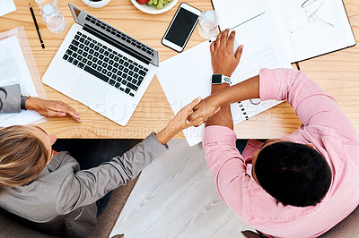 Buy stock photo High angle shot of two businesspeople shaking hands during a meeting in an office