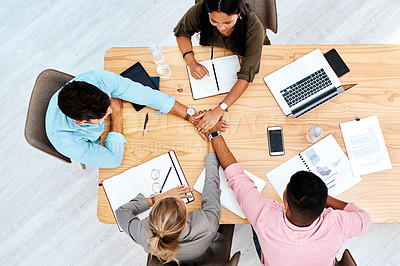 Buy stock photo High angle shot of a group of businesspeople joining their hands together in a huddle while working in an office