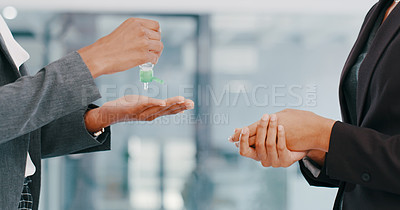 Buy stock photo Cropped shot of two businesswomen using hand sanitiser in a modern office