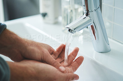 Buy stock photo Cropped shot of an unrecognisable man washing his hands with soap in the bathroom sink at home