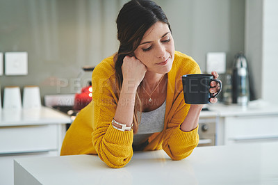 Buy stock photo Shot of a young woman having a cup of coffee in her kitchen at home