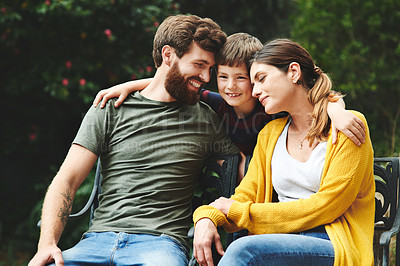 Buy stock photo Shot of an adorable little boy spending quality time with his parents in their backyard
