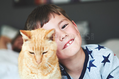 Buy stock photo Portrait of an adorable little boy and his cat relaxing on the bed with his dad in the background