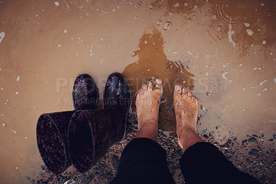 Buy stock photo Cropped shot of a woman standing a muddy puddle of water next to her rain boots