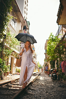 Buy stock photo Shot of a young woman walking on train tracks through the streets of Vietnam