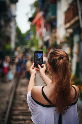 Buy stock photo Cropped shot of a young woman taking pictures while exploring a foreign city