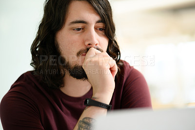 Buy stock photo Shot of a young businessman looking thoughtful while working in an office
