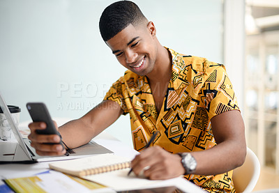 Buy stock photo Shot of a young businessman writing notes while using a cellphone in an office