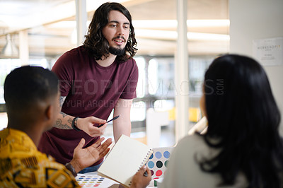 Buy stock photo Shot of a young businessman having a discussion with his colleagues in an office