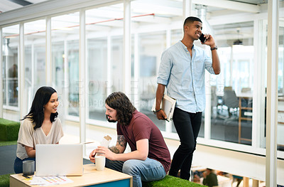 Buy stock photo Shot of two businesspeople having a discussion in an office with their colleague walking in the background
